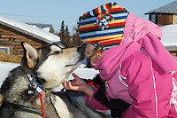 Young Ella Bird Mercer gets a kiss from a Paul Johnson dog as she pets it on Saturday morning at the Shageluk checkpoint during Iditarod 2011.