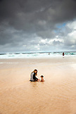 USA, Oahu, Hawaii, a mother and her baby sit in the water and play at Pipeline Beach on the North Shore