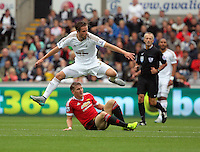 Pictured: Gylfi Sigurdsson of Swansea (TOP) avoids a tackle by Bastian Schweinsteiger of Manchester United (C) Sunday 30 August 2015<br /> Re: Premier League, Swansea v Manchester United at the Liberty Stadium, Swansea, UK
