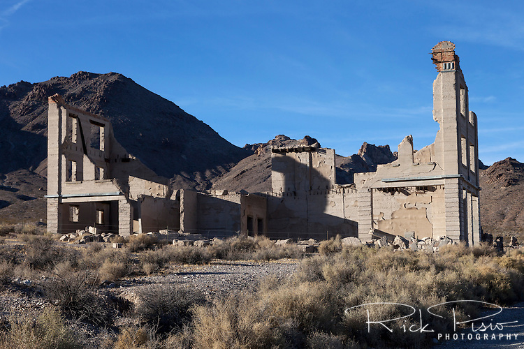 The remains of the Cook Bank Building still dominate the Rhyolite skyline just as it did when it was built in the early 1900's at a cost of $90,000. The building had marble floors imported from Italy, mahogany woodwork, electrict lights, telephone, and inside plumbing. By 1910 parts off the building were being sold off and by 1919 the building was no longer in use.
