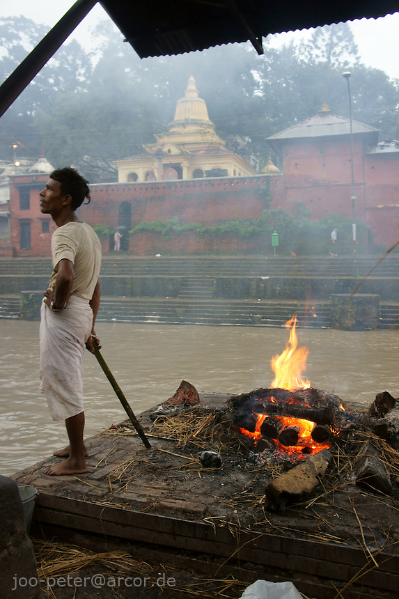 man taking rest cremation process in Ram Ghat, Pashupatinath, Kathmandu, Nepal, September 2011. Clothes of white color express mourning about death. In the background across river Bagmati  temples with dharamsala (shelters) for sadhus. Pashupatinath is Nepals most holy pilgrimage destination with many  temples and cremation area.