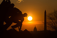 The US Marine Corps War Memorial is silhouetted against an orange sky at sunrise, with Washington landmarks in the background in Arlington, Virginia.