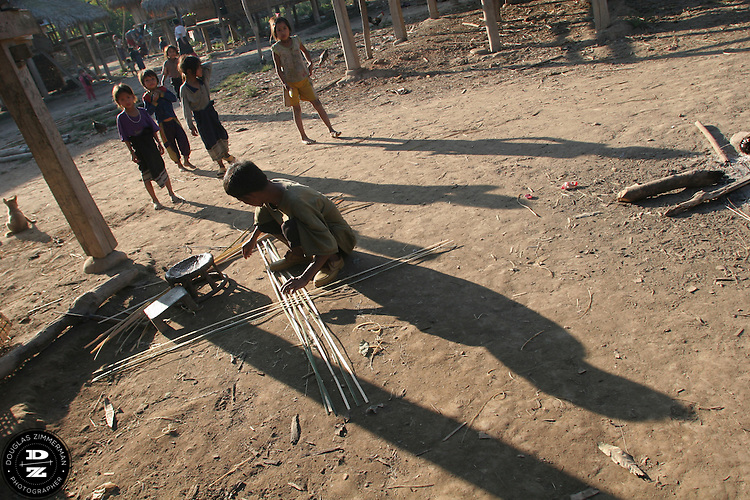 A villager work on making making a basket in the village of NamTalan, in the county of Louang Namtha, Laos.  The remote village of Nam Talan, only accessible on foot, is a village of the Kmu and Lanten ethnic groups. Photograph by Douglas ZImmerman.