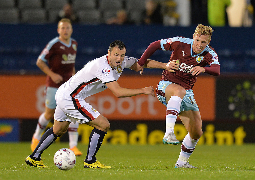 Burnley's Rouwen Hennings is tackled <br /> <br /> Photographer Dave Howarth/CameraSport<br /> <br /> Football - The Football League Sky Bet Championship - Burnley v Milton Keynes Dons - Tuesday 15th September 2015 - Turf Moor - Burnley<br /> <br /> &copy; CameraSport - 43 Linden Ave. Countesthorpe. Leicester. England. LE8 5PG - Tel: +44 (0) 116 277 4147 - admin@camerasport.com - www.camerasport.com