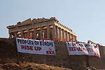 Members of the Greek Communist Party violated the gate of the Acropolis this morning and hung a banner from its sacred rock.