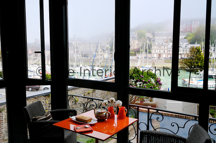 An orange lacquered table has been positioned in the glassed-in balcony to take full advantage of the harbour view