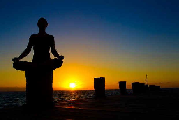 Annette Spangler begins her day in a seated yoga pose on the fisherman's pier at Puerto Morelos, Mexico.