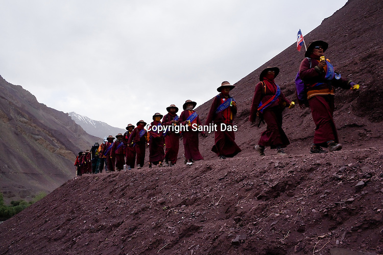 """Buddhist nuns follow His Holiness the Twelfth Gyalwang Drukpa, the head of the Drukpa Lineage during his """"Walking On The World's Rooftop"""" Pad Yatra (walk) from Manali to Ladakh. The 400 kms  walk was focused at raising awareness awareness of His Holiness' charitable projects including education, environment and cultural preservation of tribal people from the area. Accompanied on the Yatra by large numbers of Buddhist monks, nuns, foreigners and local villagers. The culmination of the Pad Yatra coincides with the colourful age-old Hemis festival in Leh, Ladakh, India."""