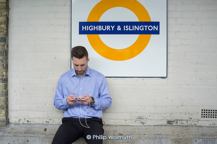 Passengers wait for a train on a platform at Highbury & Islington Overground station, London.