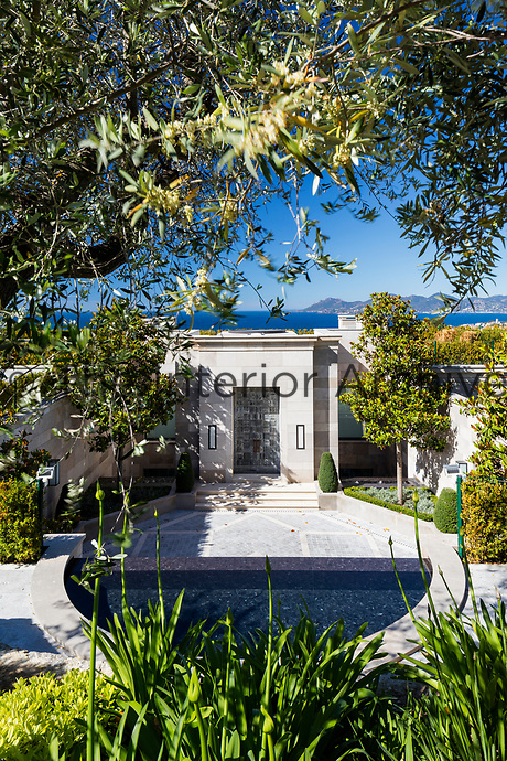 The contemporary villa sits within landscaped gardens and overlooks the bay of Cannes.