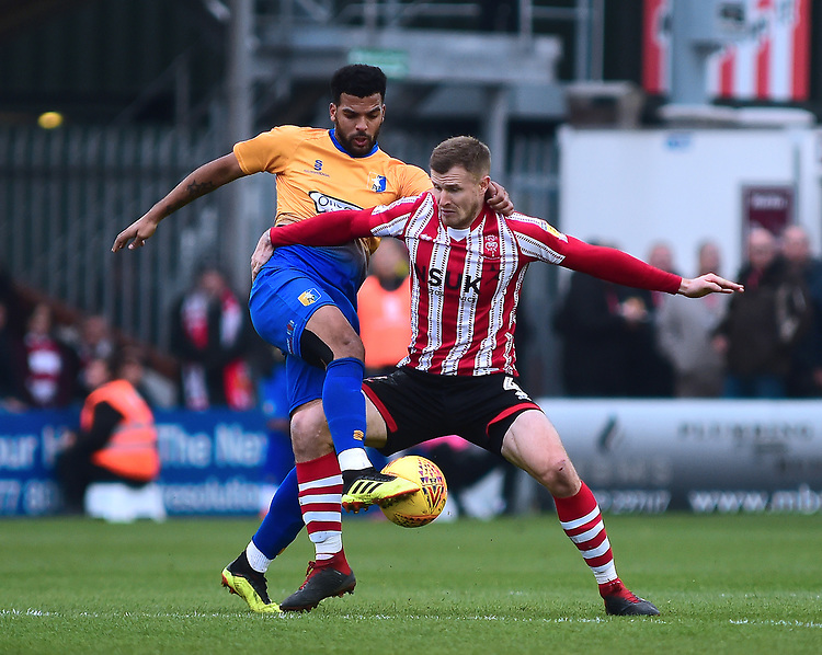 Lincoln City's Michael O'Connor vies for possession with Mansfield Town's Jacob Mellis<br /> <br /> Photographer Andrew Vaughan/CameraSport<br /> <br /> The EFL Sky Bet League Two - Lincoln City v Mansfield Town - Saturday 24th November 2018 - Sincil Bank - Lincoln<br /> <br /> World Copyright © 2018 CameraSport. All rights reserved. 43 Linden Ave. Countesthorpe. Leicester. England. LE8 5PG - Tel: +44 (0) 116 277 4147 - admin@camerasport.com - www.camerasport.com