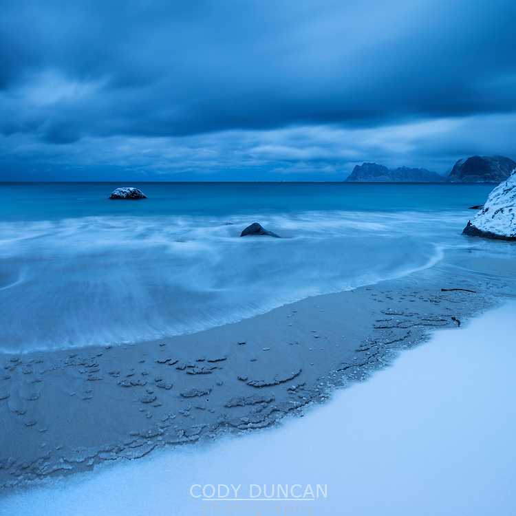 Waves wash over snow covered sand in winter at Myrland beach, Flakstadøy, Lofoten Islands, Norway