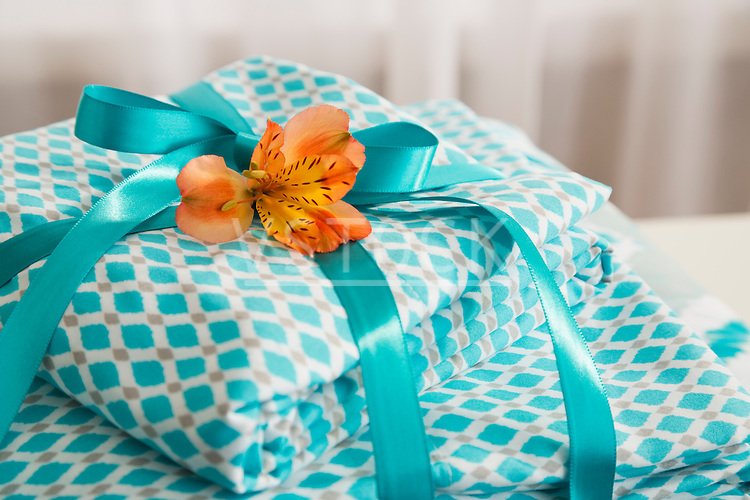 Stack of turquoise patterned bedding with turquoise ribbon and orange flower