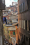 Northern Italy, Tuscany, Sienna, Cathedral, stucco rooftops, wash, steep streets,  Wooden shutters, laundry, tourists,  rooftop antennae, high tower gates, street signs, high walls, lamppost, dense building clusters