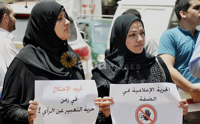 Palestinian journalists hold placards during a demonstration to protest against the closure of the al-Aqsa radio station and TV channel in the West Bank by Israeli security forces, in Gaza City on June 19, 2014. Overnight Tuesday, Israeli security forces raided the Hebron and Ramallah offices of the Al-Aqsa radio station affiliated with Hamas, confiscating equipment and documents and shutting down broadcasts. Photo by Mohammed Talatene