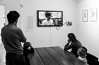 Switzerland. Canton Ticino. Meride. Museum of fossils from Monte San Giorgio. A family watch a video on a flat TV screen about palaeontological work done by scientists on the field. 6.11.2016 © 2016 Didier Ruef