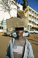 Rwanda. Kigali province. Kigali. Downtown. Town center. A streets' seller carries on his head a cardboarb box loaded with green plants for sale. American flag on his t-shirt. He stands in front of the Rwanda Tax Revenue Authority building, the National Tender Board. © 2007 Didier Ruef