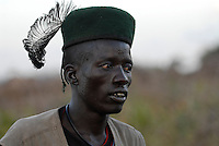 UGANDA Karamoja , Kotido, young Karimojong man in uniform shirt and hat with feather