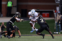 WINSTON-SALEM, NC - SEPTEMBER 13: Dazz Newsome #5 of the University of North Carolina is tackled by Nasir Greer #3 of Wake Forest University during a game between University of North Carolina and Wake Forest University at BB
