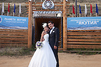 Yakutsk, Yakutia, Russia, 19/08/2011..Newly-weds Nadezhda and Vasily Fedorov outside the Permafrost Kingdom, an underground tourist attraction inspired by the extreme cold of Yakutia. The 150 metre deep complex of tunnels in the Russian permafrost are decorated with ice sculptures, a wolf-fur covered throne, an office complete with the coolest computer and telephone, a children's slide and other ingenious creations - all hewn from blocks of ice.