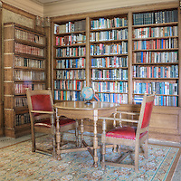 Library with table and chairs for conversation, bookcases and reading lamp.  Dating to 1927, the Masonic Retirement Center, locally known as the Masonic Home, in Des Moines, Washington is now an elegant event center available for rental.  In the historic Zenith neighborhood of the city of Des Moines. Please contact douglasorton@comcast.net regarding licensing of this image.