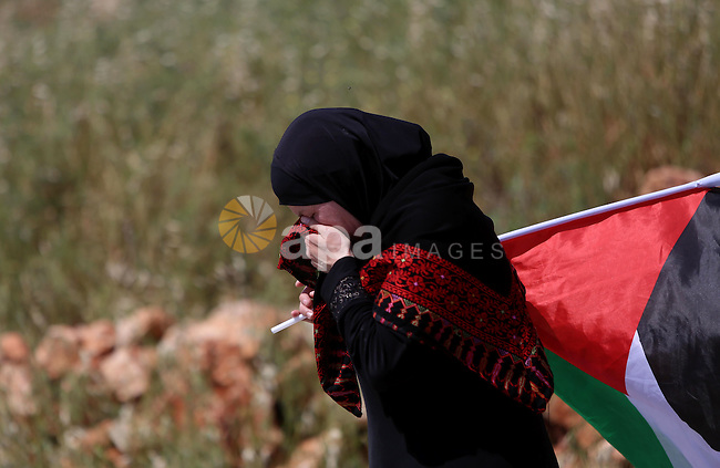 A Palestinian woman takes cover from tear gas fired by Israeli security forces during clashes following a march against Palestinian land confiscation on April 15, 2016 in the West Bank village of Nabi Saleh near Ramallah. Photo by Shadi Hatem