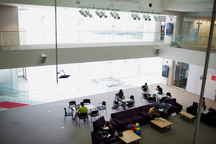 Students and others gather in the open common areas in the center of the Media Lab building at MIT in Cambridge, Massachusetts.  The area is a common place for students to chat informally, study, and collaborate.