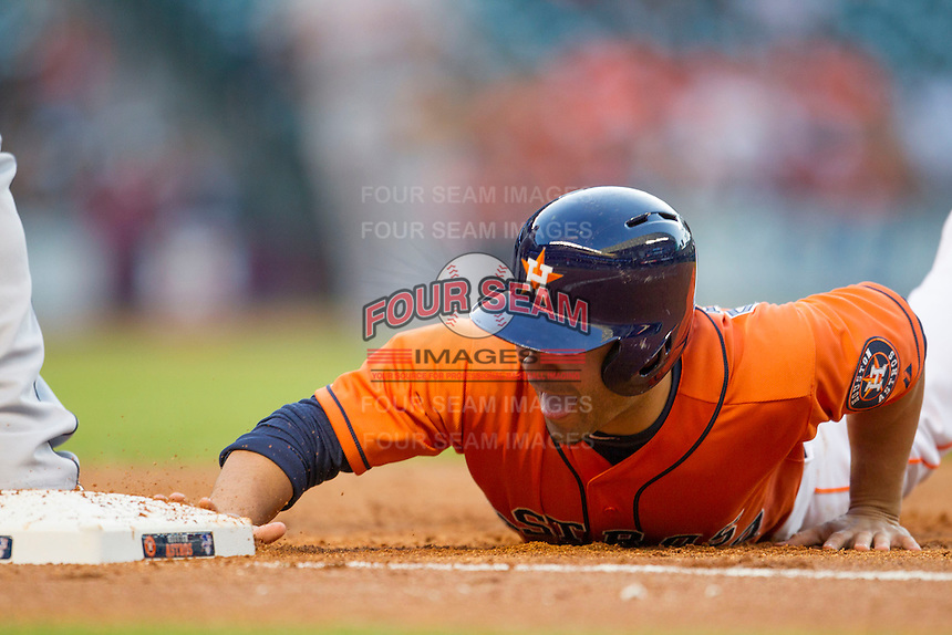 Houston Astros second baseman Jose Altuve (27) dives back to first base during the MLB baseball game against the Detroit Tigers on May 3, 2013 at Minute Maid Park in Houston, Texas. Detroit defeated Houston 4-3. (Andrew Woolley/Four Seam Images).