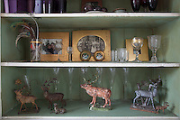Detail of deer ornaments, glassware and family photographs inside a cabinet in the living room