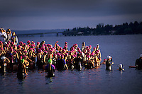 Spot-lit by a lone sunbeam, Danskin Triathletes prepare for start of swim on grey morning, Seattle