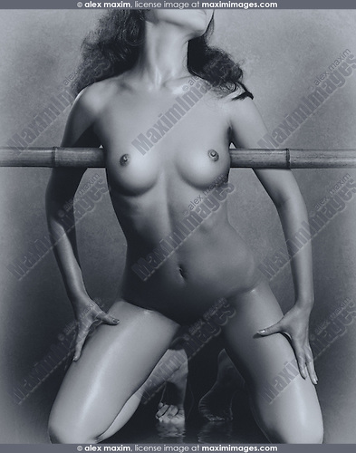 Artistic black and white erotic photo of a beautiful naked asian woman about to be tied up to bamboo.