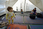 A refugee woman and her child inside a tent in a city park on the Greek island of Chios. The park is full of tents sheltering refugees who crossed the Aegean Sea in small boats from Turkey. They were registered and provided with food and shelter in a reception center built with support from International Orthodox Christian Charities, a member of the ACT Alliance. Many of them then move to the city park where they await a ferry to take them to Athens and then on toward western Europe. Hundreds of thousands of refugees and migrants have passed through Greece in 2015.