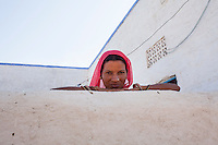 Suki (not her real name), leans on the wall outside her house in Jhaju village, Bikaner, Rajasthan, India on 4th October 2012. Now 20, Suki was married off at age 12, but only went to live with her husband when she was 14. The three sisters, aged 10, 12, and 15 were married off on the same day by their maternal grandfather while their father was hospitalized. Her husband died three years after she moved in, leaving her with a daughter, now 6, and a son, now 4. She has no parents-in-laws and thus returned to her parents house after being widowed because her brother-in-law, who had become the head of the family after his brother's death, had refused to allow Suki to inherit her deceased husband's fair share of agriculture land. Although Suki's father wants her to remarry, she refuses to, hoping instead to be able to support her family through embroidery and tailoring work. The family also makes hand-loom cotton to subsidize their collective household income. Photo by Suzanne Lee for PLAN UK