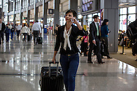 Businesswoman pulls suitcase while holding conversation on mobile cell phone at the Austin–Bergstrom International Airport (ABIA).