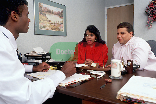 Young couple meets with physician in his office