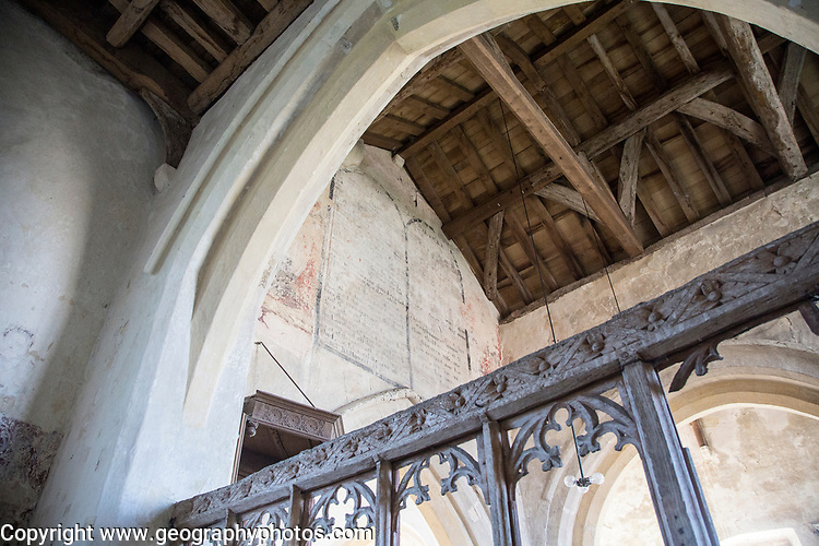 Building interior medieval church architectural feature, Inglesham, Wiltshire, England decalogue of 19th century prayer overlain on medieval paintings on chancel wall low able view of wooden roof and carved screen
