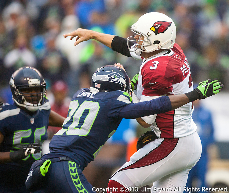Arizona Cardinals quarterback Carson Palmer (3) passes under pressure by Seattle Seahawks cornerback Jeremy Lane (20) CenturyLink Field in Seattle, Washington on December 22, 2013.    Palmer completed 13 of 25 passes for 178 yards, three four interceptions and one touchdown in the Cardinals 17-10 win over the Seahawks. ©2013. Jim Bryant Photo. ALL RIGHTS RESERVED.