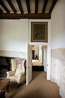 An antique tapestry hangs above the open door of the main living room and a seagrass floor covering takes the place of what would have been rush matting