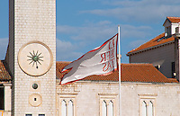The Clock tower and loggia loge Luza on the central square. Detail of solar clock and town flag banner with slogan text Libertas against blue sky Dubrovnik, old city. Dalmatian Coast, Croatia, Europe.