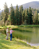 USA, Montana, woman fly fishing for trout in a lake, Mountain Sky Guest Ranch