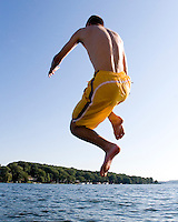 A teenager jumping into a lake.