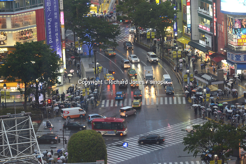 PEOPLE ARE CROSSING WITH UMBRELLA ON SHIBUYA CROSSING NEAR SHIBUYA STATION, TOKYO