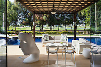 The covered terrace area beside the swimming pool has plenty of seating arranged around a coffee table. The classic pieces include a Nemo chair by Fabio Novembre, Masters chairs by Philippe Starck and a Tron armchair by Dror Benshetrit.