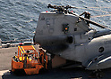 PACIFIC OCEAN (March 29, 2011) Marines load humanitarian assistance supplies into a CH-46E Sea Knight helicopter on the flight deck of the forward-deployed amphibious assault ship USS Essex (LHD 2). Essex, with the embarked 31st Marine Expeditionary Unit (31st MEU), is operating off the coast of Kesennuma in northeastern Japan to support Operation Tomodachi.  (Photo by U.S. Navy/AFLO) [0006]