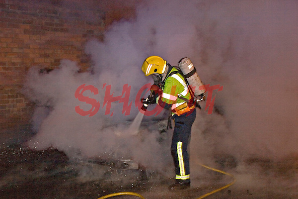 Ford KA car well alight being extinguished by firefighters wearing BA Warwickshire UK. This image may only be used to portray the subject in a positive manner..©shoutpictures.com..john@shoutpictures.com