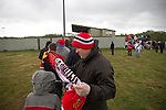 A man wrapping a scarf around a boy outside Key's Park prior to the Hednesford Town versus FC United of Manchester Northern Premier League premier division play-off final. The match would decide which club were promoted to the Blue Square Conference North. Hednesford won the game by 2 goals to 1 in front of a stadium record attendance of 4412 spectators.