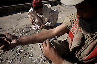a heroin addict injects himself with a dose of heroin while another heroin addict ( in the background ) prepares his dose  on a roof top  in the city of Rawalpindi, Pakistan on friday November 28 2008.///..While Bangladesh, India, Nepal and Maldives all suffer from drug consumption, Pakistan is the worst victim of the drug trade in South Asia. Today, the country has the largest heroin consumer market in the south-west Asia region..The drug addicts resort to crime for generating income for the purchase of narcotics. The situation is becoming serious due to the number of heroin addicts in the country. An alarming rate of increase of 100,000 addicts per year is highly dangerous to society. The drug addicts are affecting nearly 20 million dependents and family members with psychological, social, and economic repercussions.