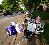 Jo Ann Wardein laughs Thursday, May 14, 2020, as she waves at passing cars on Tall Oaks Drive during a parade for 2020 Fayetteville High School graduates who attended or live in the Root Elementary School district. The parade wound through several neighborhoods around Root Elementary before ending at the school. Visit nwaonline.com/200515Daily/ for today's photo gallery.<br /> (NWA Democrat-Gazette/Andy Shupe)