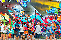 A walking tour visits the murals in the Bushwick neighborhood of Brooklyn in New York on Saturday, August 16, 2014.   The neighborhood is undergoing gentrification changing from a rough and tumble mix of Hispanic and industrial to a haven for hipsters and a destination for tourists, forcing many of the long-time residents out because of rising rents. (© Richard B. Levine)