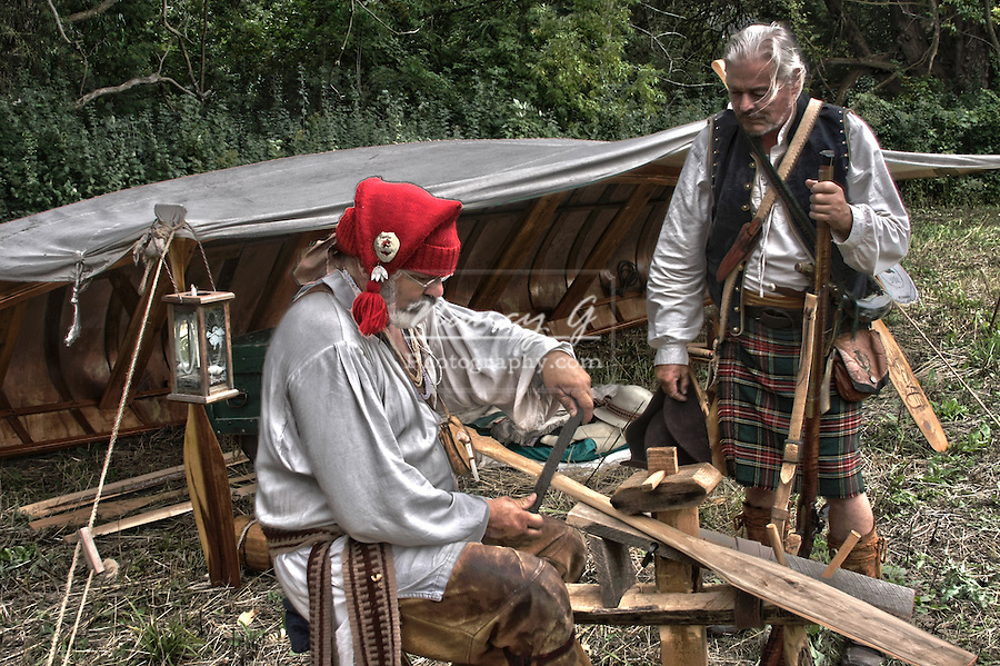 French Voyageurs canoe camp in the woods with a voyageur shaving a paddle